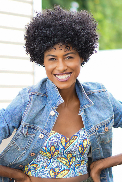 Angelica Guillen smiling wearing a blue jean jacket and flower print blouse
