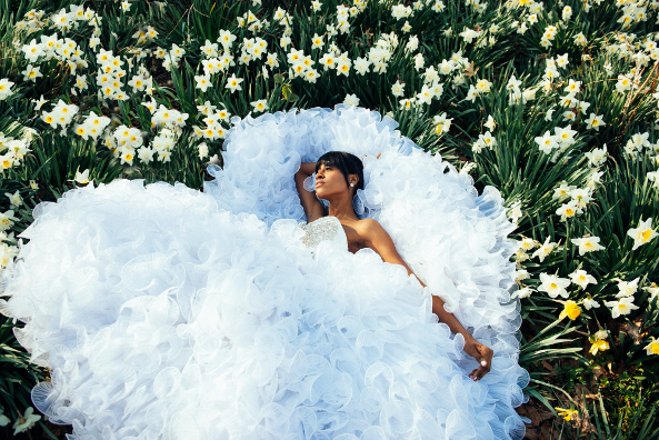 Angelica Guillen laying down in a flower field wearing a bridal dress